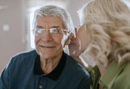 Wife talking to husband with hearing aid in ear