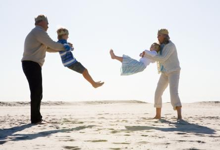 Grandparents playing with grandchildren on beach